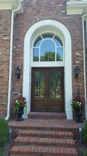 Exterior photo of a door and window installation with a complex overhead arched window
