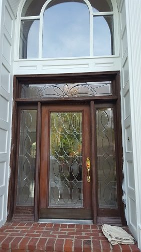 Exterior photo of a door and window installation with an intricate line-work design glass inlay and a complex overhead arched window