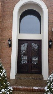 Photo of a double door installation with an intricate line-work design and a large arched window overhead