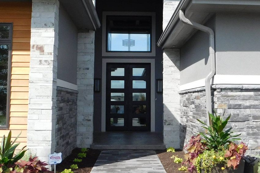 Exterior photo of a very modern double door entry way with a large overhead window